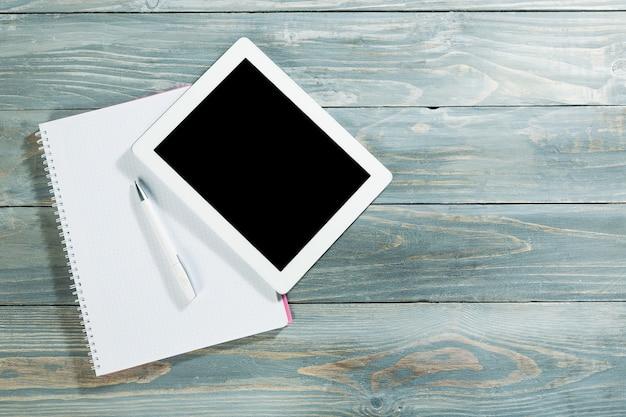 메모장과 펜이 있는 나무 태블릿의 디지털 태블릿
