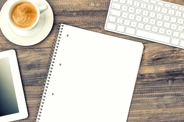 디지털 태블릿 pc, 키보드 및 나무 테이블에 커피 한 잔. 복고 스타일 톤 그림
