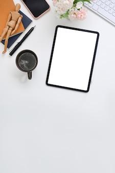 白いオフィスの机の上にデジタルタブレット、スマートフォン、コーヒーカップ、ノートブック、観葉植物。