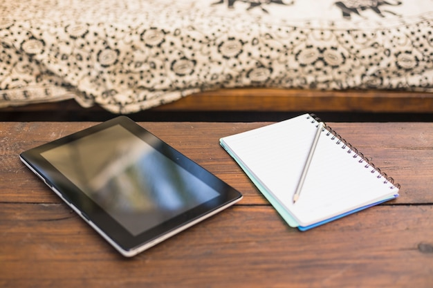 Digital tablet and spiral notebook with pencil over the wooden table