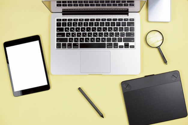 Digital tablet; stylus; graphic digital tablet; laptop and magnifying glass on yellow backdrop