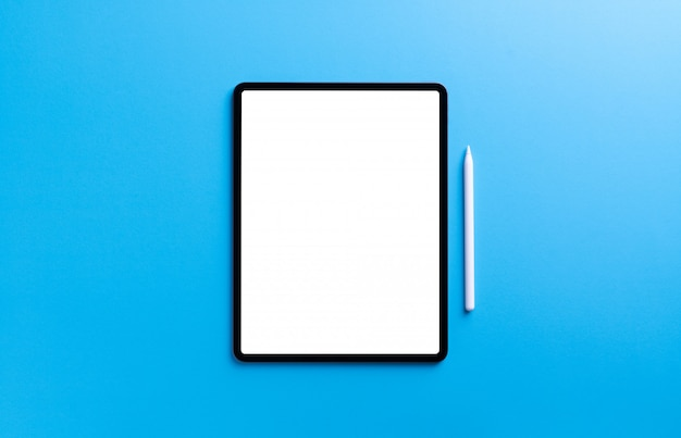 Digital tablet and stylus pen on light blue wall