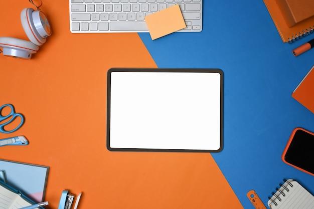 青とオレンジの2トーンの背景に事務用品に囲まれたデジタルタブレット。