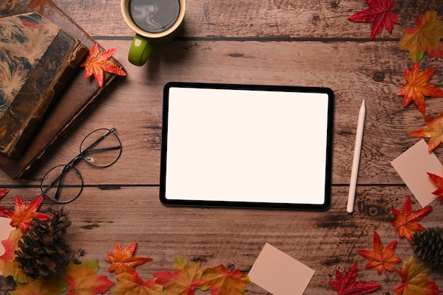 디지털 태블릿, 빈티지 책, 안경, 커피 컵, 가을 단풍 나무 배경에 나뭇잎.