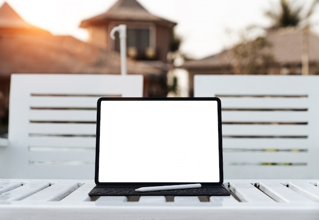 Digital tablet white screen on table at sunset
