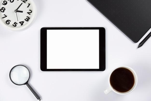目覚まし時計付きデジタルタブレット。虫眼鏡;コーヒーカップと白い背景の上のスタイラスとグラフィックのデジタルタブレット