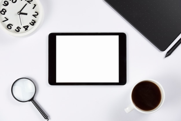 Digital tablet with alarm clock; magnifying glass; coffee cup and graphic digital tablet with stylus on white background