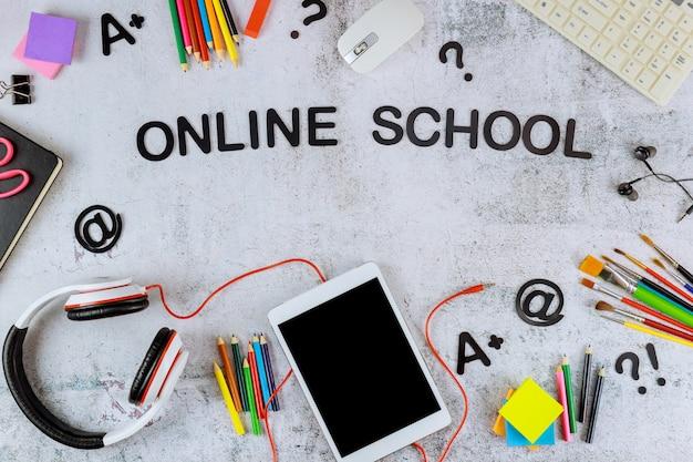 Цифровой планшет с черным экраном-макетом для школьного образования и художественных принадлежностей на белом фоне.