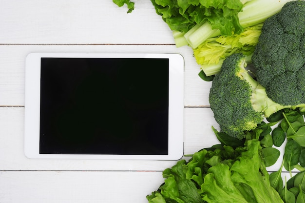 Digital tablet with black screen and vegetables, healthy food concept