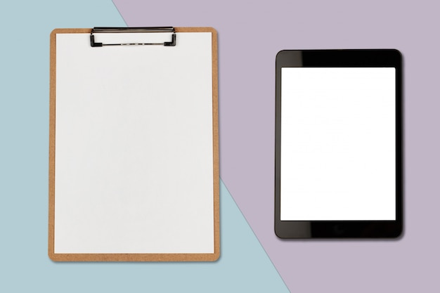 Digital tablet with blank screen and clipboard on pastel color background, flat lay photo