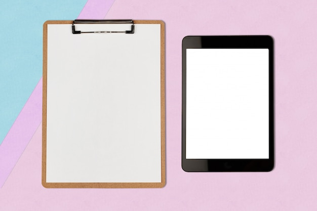 Digital tablet with blank screen and clipboard on pastel color background
