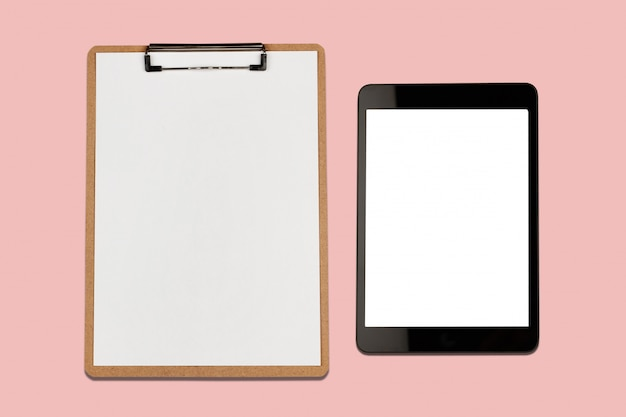 Digital tablet with blank screen and clipboard on pink background