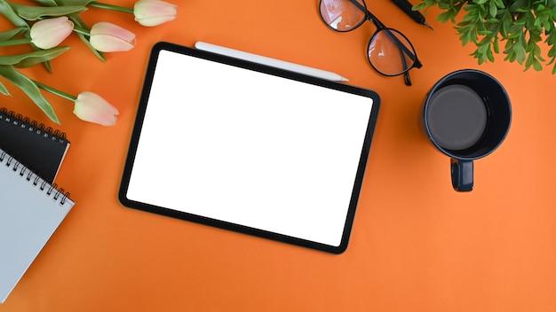 Цифровая таблетка с пустым экраном, кофейной чашкой, очками и предпосылкой апельсина тетради. Premium Фотографии
