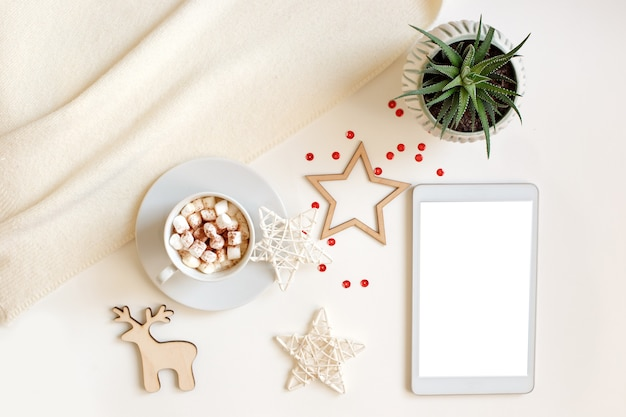 A digital tablet with a blank screen lies on a white table surrounded by flat wooden christmas