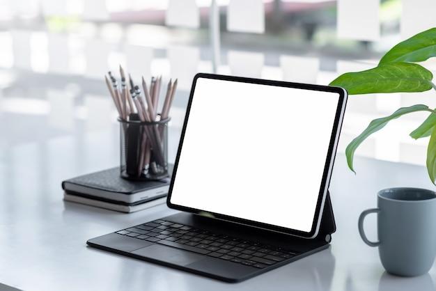 Цифровой планшет с пустым экраном на столе в офисе.