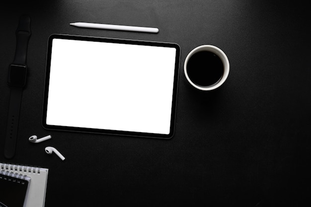 Цифровой планшет с пустым экраном, стилусом, беспроводным наушником и кофейной чашкой на темном столе.