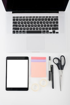 Digital tablet with blank white screen; laptop and stationeries on white background