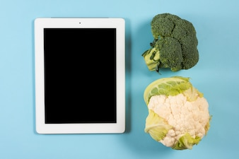 Digital tablet with broccoli and cauliflower on blue background