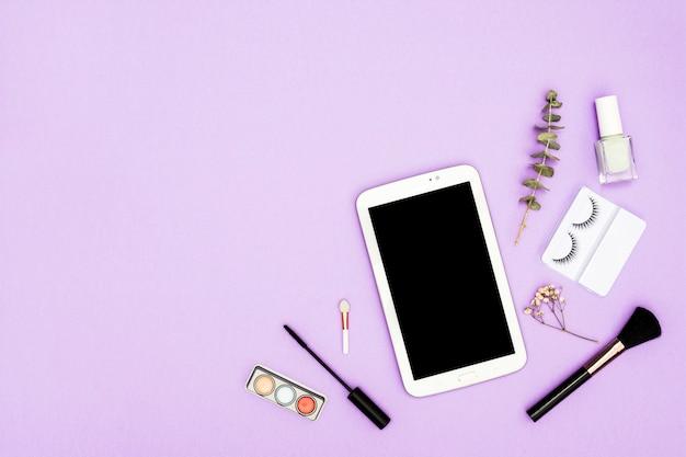 アイシャドウパレット付きデジタルタブレット。化粧用ブラシ;ネイルポリッシュボトル。紫色の背景にマスカラーブラシとマニキュア液ボトル