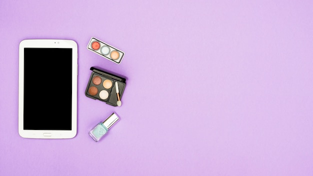 Digital tablet with eyeshadow palette and nail polish bottle on purple background