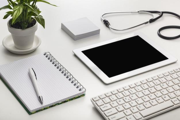 Цифровой планшет с зеленым растением, ручка, блокнот и стетоскоп на столе в офисе