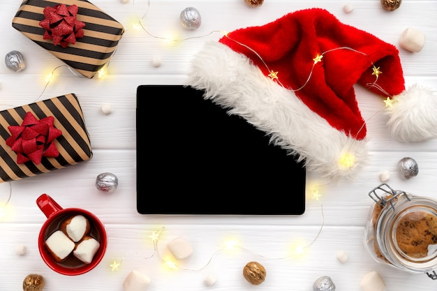 Digital tablet with hot chocolate and gifts on white wood. christmas flat lay
