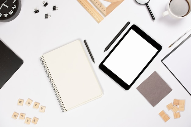 Digital tablet with stylus and office supplies on white background