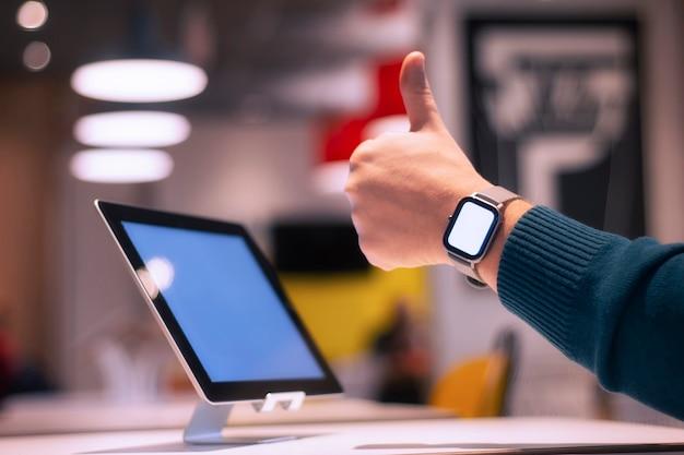 テーブルの上の白い画面とokサインをしている男の手にスマートウォッチを備えたデジタルタブレット