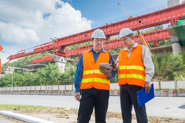 Инженер или архитектор консультируются с digital tablet, чтобы контролировать или управлять проектом автомагистрали или шоссе