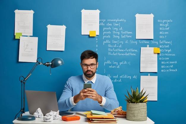 彼の仕事に夢中になっているデジタル技術の専門家または愛好家は、携帯電話を使用し、多くの論文に囲まれ、デスクトップでポーズをとる最新のデバイスで動作します