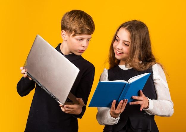학습을 위한 디지털 기술. 어린 아이들은 학교에서 새로운 기술을 사용합니다. 어린 소녀와 소년은 it 책과 노트북을 들고 있습니다. 교육의 기술. 교육 기술. 이러닝. 온라인 과정.