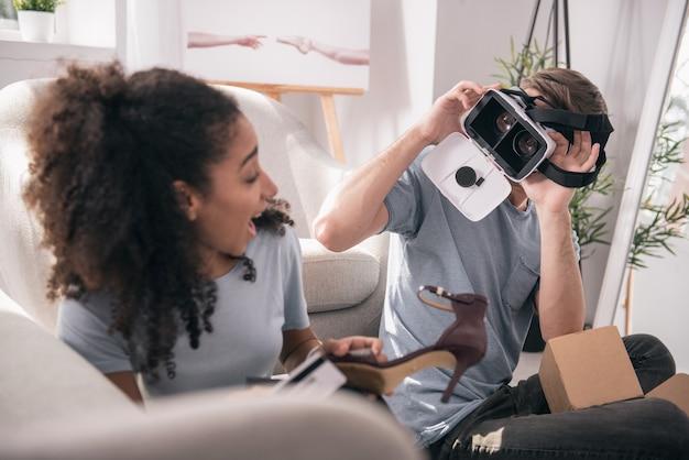 デジタル技術。彼のガールフレンドを見ながら3dメガネをかけて幸せな素敵な男