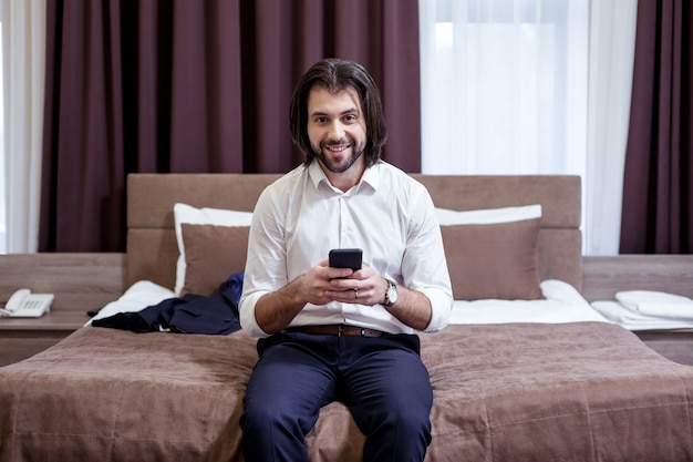 Digital technology. joyful good looking man using his mobile device while sitting on the bed
