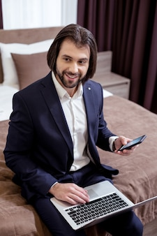 Digital technology. positive successful businessman holding his smartphone while sitting with a laptop