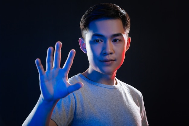 デジタル技術。デジタル画面の前に立っている間彼の前を見てスマートなアジア人男性