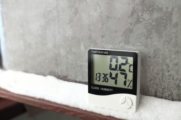 Цифровой термометр на окне со снегом. электронный термометр и гигрометр для контроля температуры и влажности
