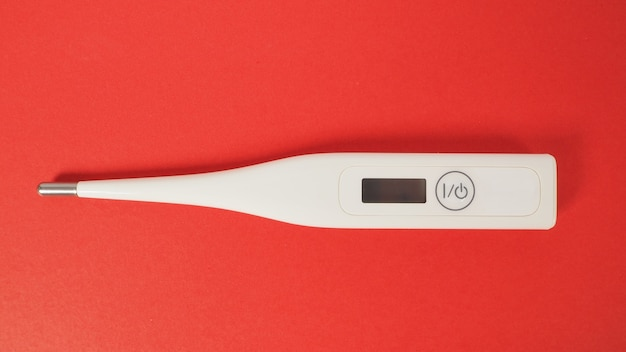 Digital thermometer on red background.