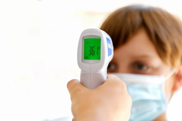 Digital thermometer scanning a boy's body temperature