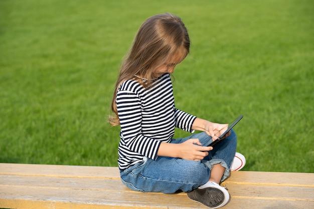 デジタル的にあなたのもの。小さな子供は公園のベンチに座ってタブレットを使用します。タブレットpcテクノロジー。現代の生活。新技術。オンラインゲーム。ソーシャルネットワーク。仮想世界。楽しさと娯楽のためのテクノロジー。