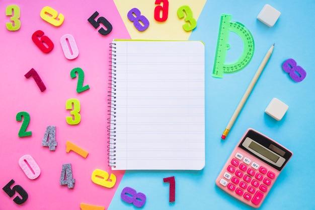 Цифры и канцелярские принадлежности вокруг ноутбука