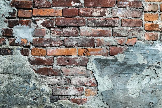 Обветшалая красная кирпичная стена, старый разрушенный фасад. городское grunge stonewall, разрушенное здание, предпосылка архитектуры цемента.