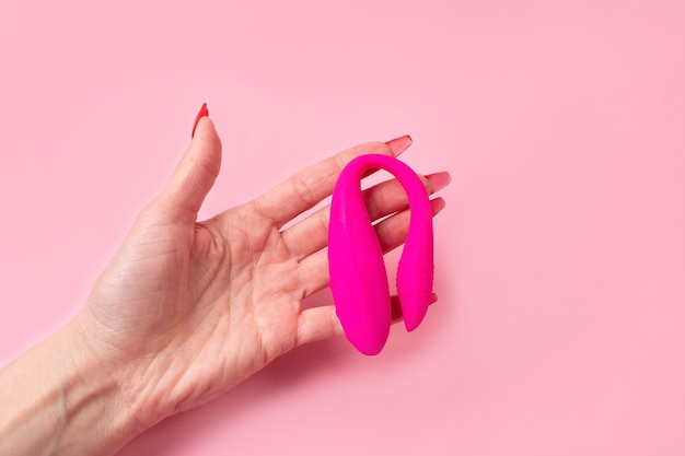 The dildo in hand on a pink background, sex toy