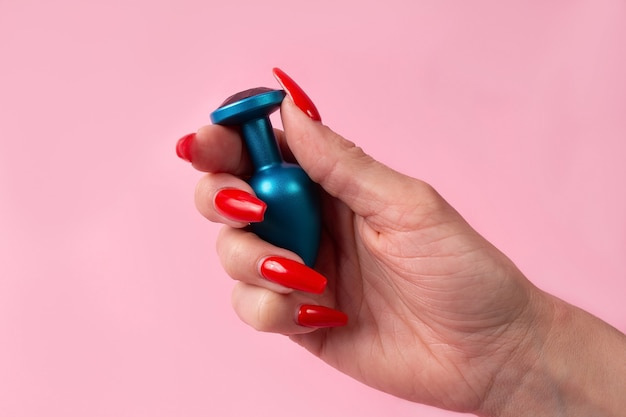 The dildo in hand on a pink wall, sex toy