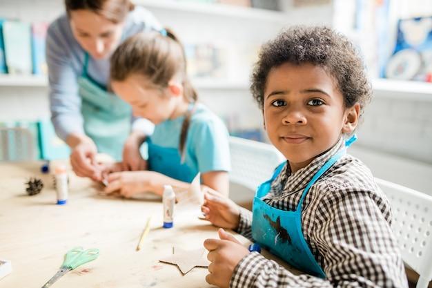 レッスンで手作りのカートンハロウィーンの装飾を準備する青いエプロンで勤勉なアフリカの少年