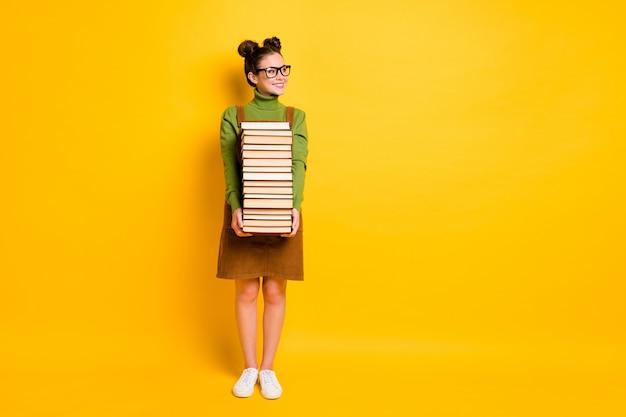 Прилежная жизнерадостная девушка-ботаник несет много книг в школу 1 сентября, осень