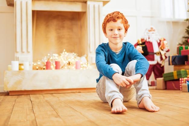 勤勉な子供。自宅で陽気な笑顔で木の床でリラックスしている生姜の少年のローアングルショット。
