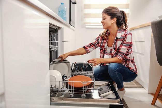 Прилежная хозяйка кладет посуду в посудомоечную машину.