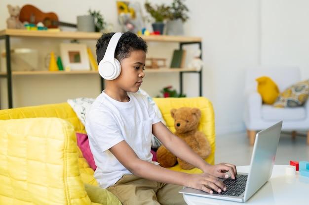 Прилежный школьник младшего возраста в наушниках нажимает кнопки клавиатуры ноутбука во время учебы за столом в домашней обстановке