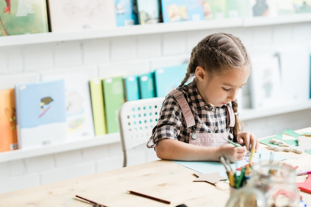 絵画のレッスンで個別に作業しながら机でクリスマスの絵を描く勤勉な女子高生