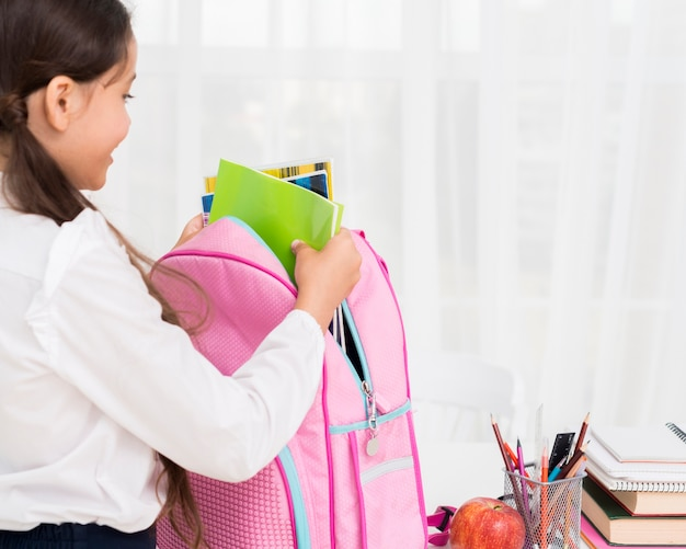 Diligent schoolgirl packing schoolbag at desk